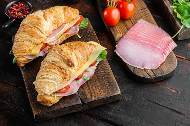 Francuskie jedzenie na śniadanie. pieczone kanapki rogalik z zieleniną szynki i sera, z ziołami i składnikami, na tle stary ciemny stół drewniany