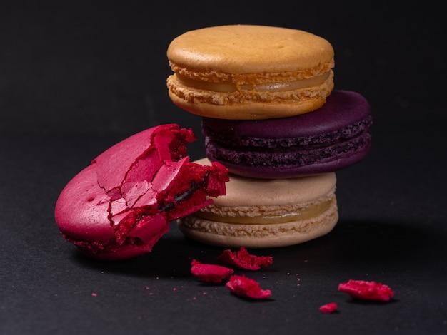 Francuskie kolorowe makaroniki kolorowe z nadzieniem na czarnym stole. gotowanie ciasteczek w domu.