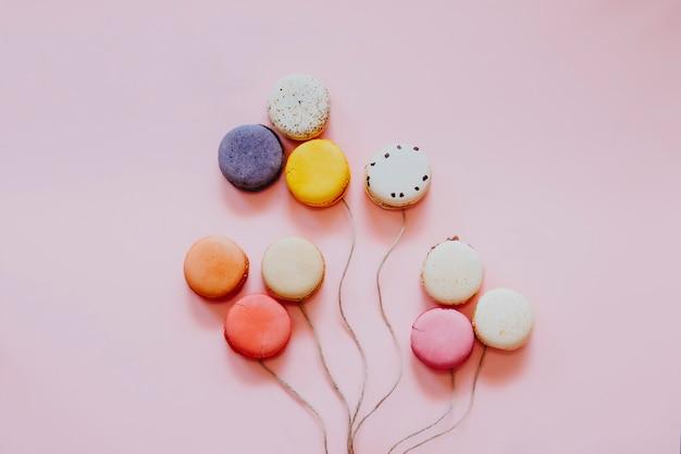 Francuskie kolorowe makaroniki. małe słodkie ciasteczka na białym tle. deser. płaskie ukształtowanie makaroników w kształcie balonów. szczęśliwa koncepcja urodziny i walentynki kreatywne minimalne pojęcie.