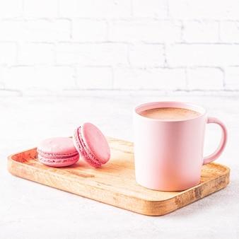 Francuskie makaroniki i filiżanka kawy na drewnianej tacy.