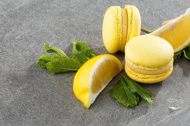 Francuskie makaroniki na białym tle. selektywne ustawianie ostrości. piękni żółci macaroons z cytryną i mennicą na popielatym kamiennym tle