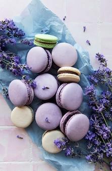 Francuskie makaroniki o lawendowym smaku i świeżych lawendowych kwiatach na kafelkowym tle