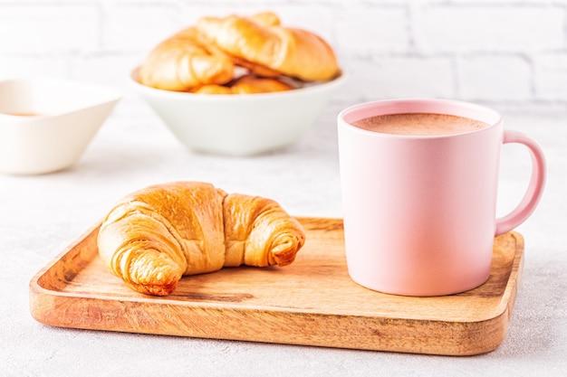Francuskie rogaliki i filiżankę kawy na drewnianej tacy.