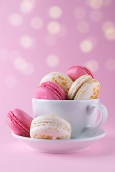 Francuskie różowe i białe pyszne macarons w filiżance kawy