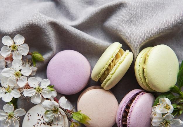 Francuskie słodkie makaroniki kolorowe odmiany na szarym tekstylnym tle z wiosennym kwiatem