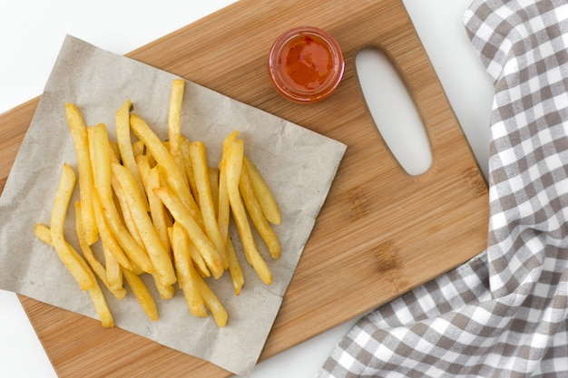 Francuskie smażone ziemniaki na deski do krojenia z sosem widok z góry.