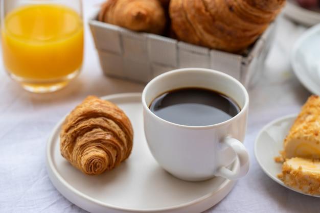 Francuskie śniadanie, gorąca kawa z rogalikami i sokiem pomarańczowym. dzień dobry koncepcja.