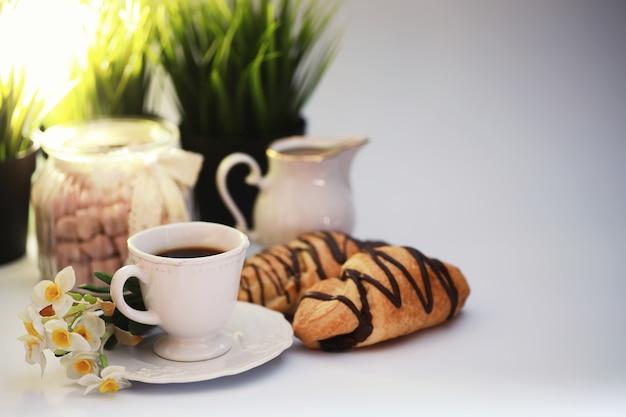 Francuskie śniadanie na stole. rogalik kawowy z czekoladą i karafką ze śmietanką. świeże wypieki i kawa bezkofeinowa.