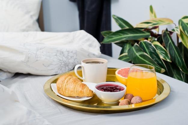 Francuskie śniadanie w hotelu. kawa, dżem, rogalik, sok pomarańczowy, grejpfrut, liczi.
