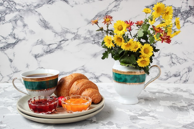 Francuskie śniadanie z rogalikami, dżemem morelowym, dżemem wiśniowym i filiżanką herbaty, czerwonymi i żółtymi kwiatami