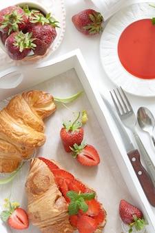 Francuskie śniadanie z rogalikiem i dżemem truskawkowym na białym tle