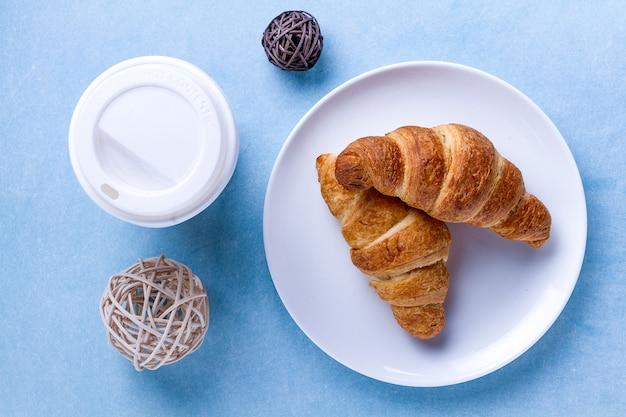 Francuskie śniadanie ze świeżo upieczonymi rogalikami i filiżanką gorącej kawy