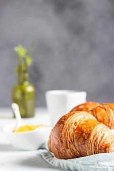 Francuskie śniadanie ze świeżymi wypiekami rogaliki z kawą i dżemem