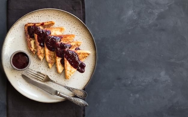 Francuskie tosty z dżemem jagodowym na szarym tle betonu. widok z góry. miejsce na tekst.