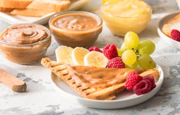 Francuskie tosty z masłem migdałowym i owocami. chleb tostowy z różnorodnym masłem orzechowym. domowy chleb tostowy z dżemem i masłem orzechowym na drewnianym stole na śniadanie.