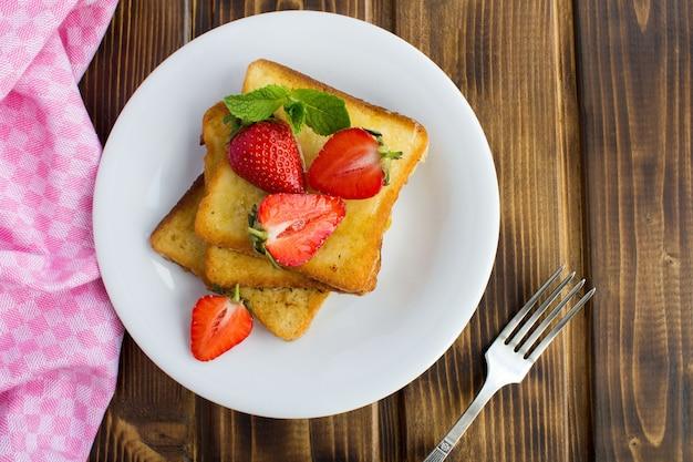 Francuskie tosty z truskawkami białym talerzu na brązowym drewnianym stole widok z góry miejsce kopiowania zbliżenie