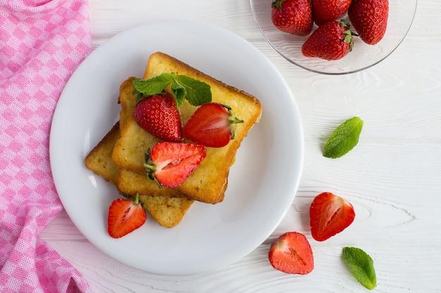 Francuskie tosty z truskawkami i miodem na białym talerzu