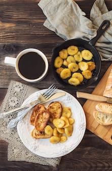 Francuskie tosty ze smażonymi bananami na śniadanie na rustykalnym drewnianym tle. widok z góry.