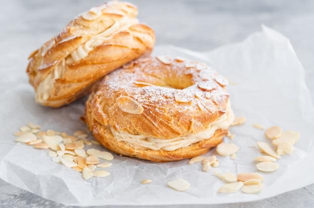 Francuskie tradycyjne ciasto paris brest z kremem pralinowym, cukrem pudrem i płatkami migdałów