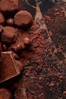 Francuskie trufle czekoladowe z kakao w proszku z bliska na ciemnym tle marmuru.
