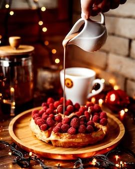Francuskie wafle z malinami posypane rozpuszczoną czekoladą