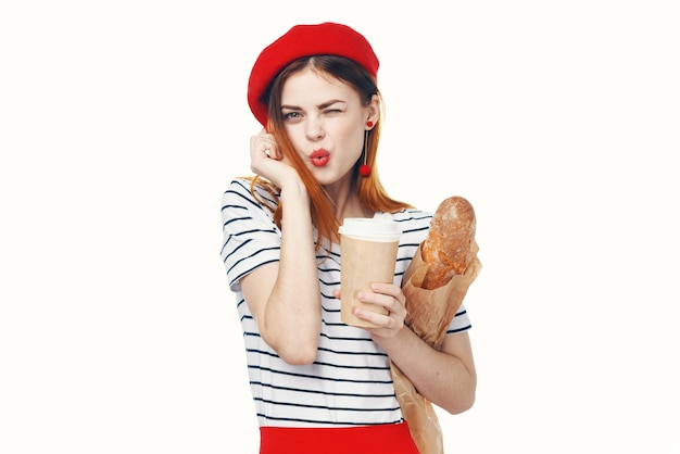 Francuzka w czerwonym kapeluszu z bochenkiem kawy i niebieskim tłem