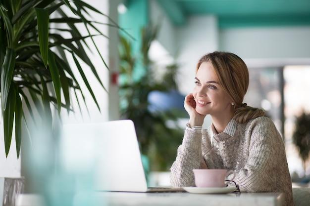 Frasobliwy młoda dama siedzi cafe