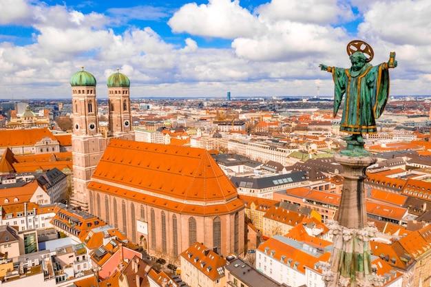 Frauenkirche otoczona budynkami w słońcu i pochmurnym niebie w monachium, niemcy