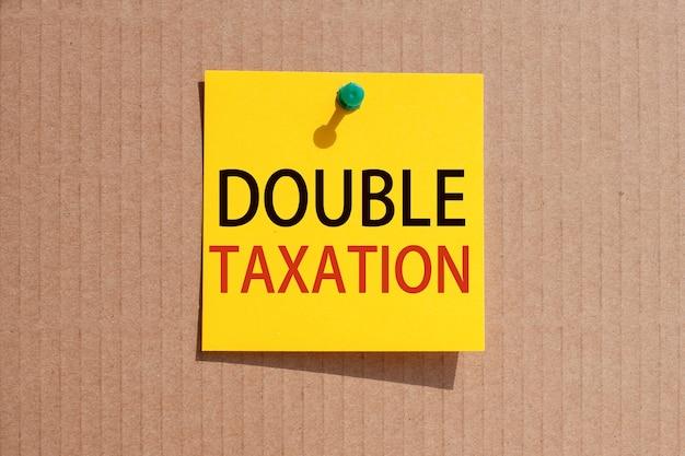 Fraza biznesowa - podwójne opodatkowanie - napisana na żółtym kwadratowym papierze i przypięta na tekturze