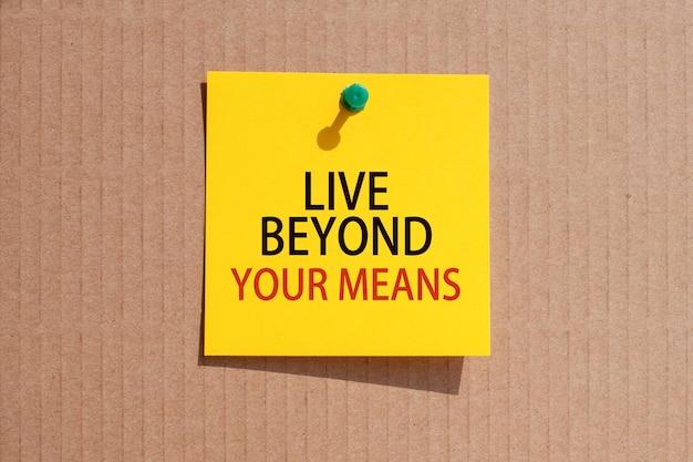 Fraza biznesowa - żyj ponad swoje możliwości - napisana na żółtym kwadratowym papierze i przypięta na tekturze, koncepcja