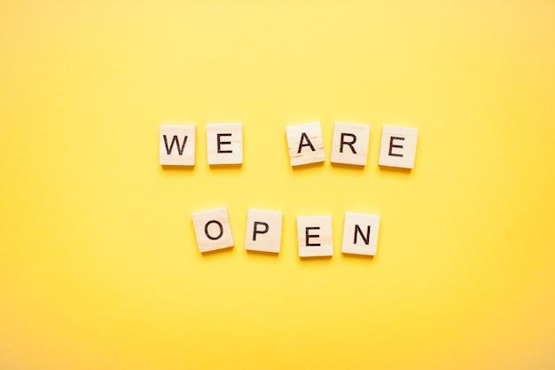 Fraza jesteśmy otwarci wykonana z drewnianych klocków na jasnożółtym tle