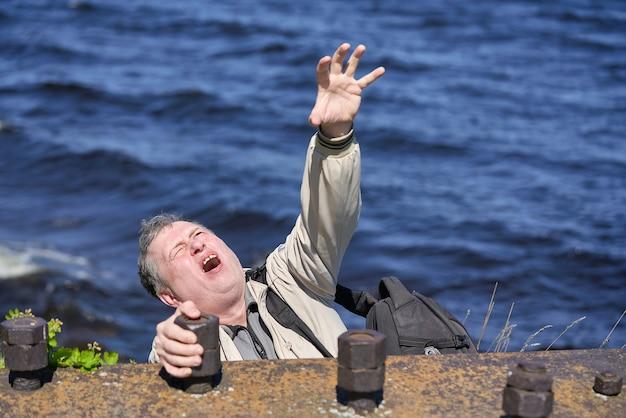 Freak trzyma ręce na krawędzi urwiska nad wodą