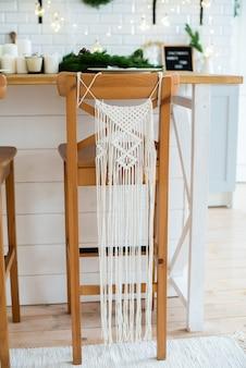 Frędzla. majsterkowanie. wystrój salonu. makrama na drewnianym krześle. przytulny styl rustykalny.