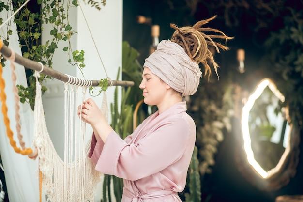 Frędzla. młoda kobieta w nakrycia głowy tkania makrama