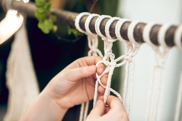 Frędzla. zamknij się obraz kobiecych rąk tkania makramy
