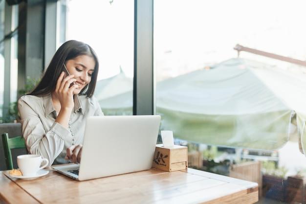 Freelance kobieta pracuje z laptopem w sklep z kawą
