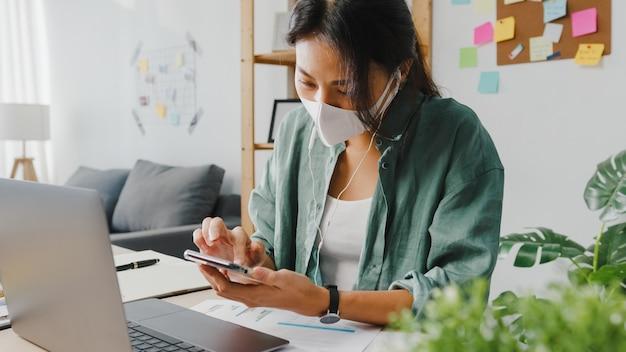 Freelancer asia kobiety noszą maskę na twarz, korzystając ze smartfona, robiąc zakupy online za pośrednictwem strony internetowej, siedząc przy biurku w salonie.