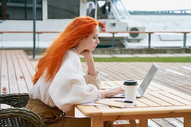 Freelancer dziewczyna siedzi w kawiarni na ulicy i pracuje zdalnie na laptopie.