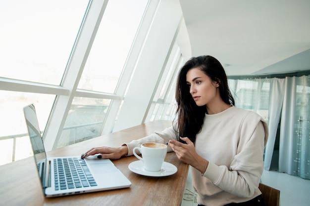 Freelancer kobieta pracuje na laptopie i pisze na smartfonie do klienta