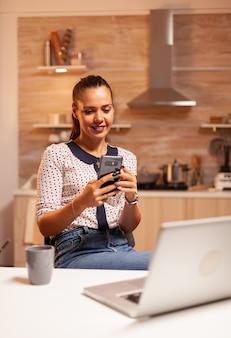 Freelancer kobieta rozmawia przez telefon podczas pracy w domu późno w nocy. pracownik korzystający z nowoczesnych technologii o północy wykonujący nadgodziny w pracy, biznesie, karierze, sieci, stylu życia, wirele