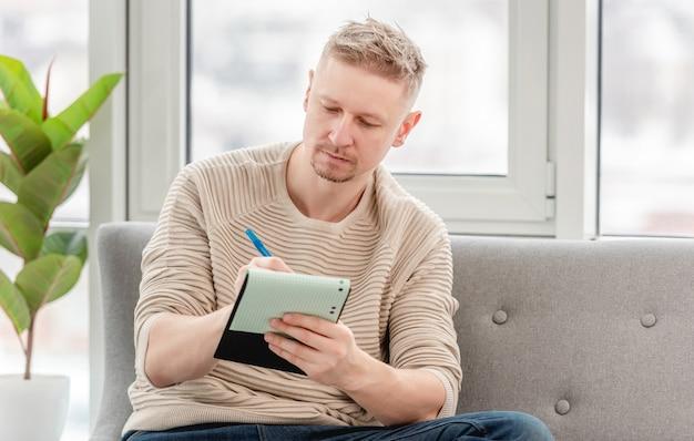Freelancer mężczyzna siedzi na kanapie i pisze w notatniku w słoneczny dzień