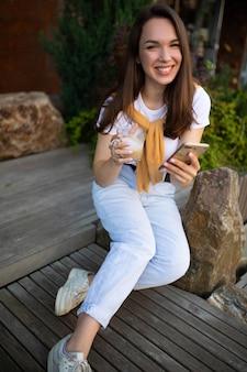 Freelancer młoda kobieta siedzi w parku i cieszy się przerwą na kawę z telefonem w dłoniach.