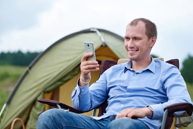 Freelancer młody człowiek siedzi na krześle i przy użyciu smartfona