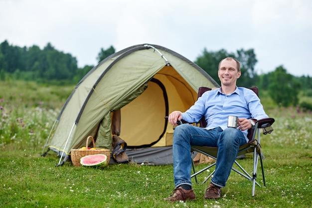 Freelancer młody człowiek siedzi na krześle i relaks przed namiotem na kempingu w lesie lub na łące