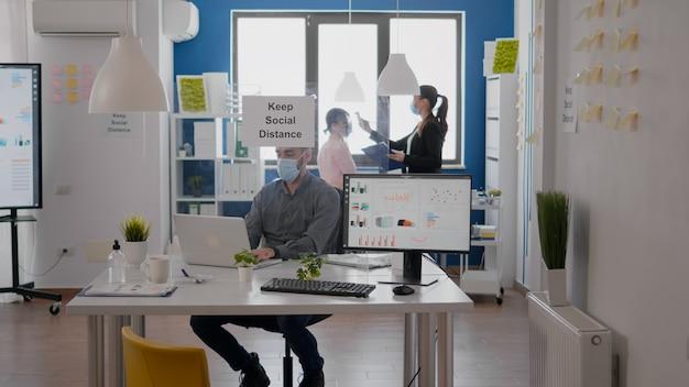 Freelancer noszący maskę ochronną, sprawdzający temperaturę zespołu za pomocą termometru medycznego. współpracownicy szanują dystans społeczny w nowym, normalnym biurze firmy, aby uniknąć infekcji wirusem
