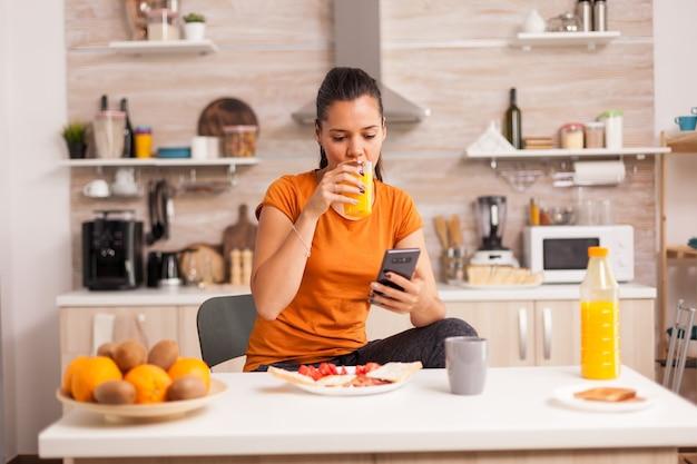 Freelancer pijący rano sok pomarańczowy i robiący zakupy online