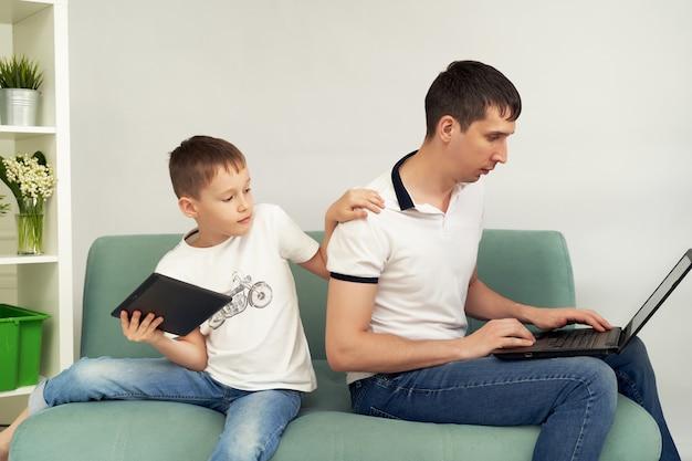 Freelancer pracuje w domu w komfortowych warunkach. człowiek stara się pracować, dziecko uniemożliwia ojcu pracę.