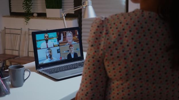Freelancer rozmawiający z klientami podczas rozmowy wideo o północy z domu. spotkanie firmowe z wykorzystaniem nowoczesnych technologii, laptop późno w nocy, technika, agencja, doradca, praca, dyskusja.