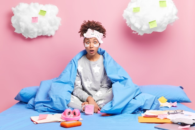 Freelancer siedzi w pozycji lotosu na wygodnym łóżku wpatruje się pod wrażeniem nosi piżamę przygotowuje raport otoczony papierami i karteczkami na różowo