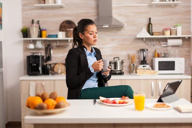 Freelancer słuchający mówcy motywacyjnego podczas picia kawy przed pójściem do pracy